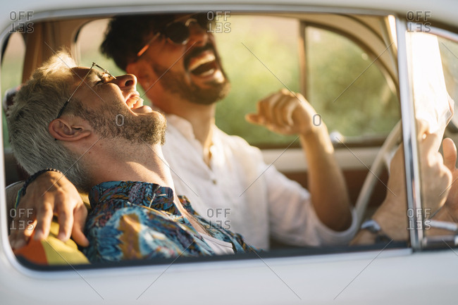 Two young guys laughing and holding map while sitting inside retro car during nice travel