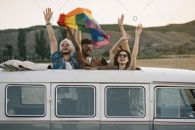 Group of cheerful diverse people standing inside retro van with opened roof and holding LGBT flag over heads while travelling in nature together