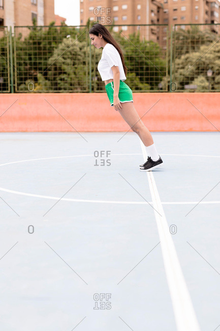 Attractive female in sportswear falling forward straight on outdoors sports ground in city