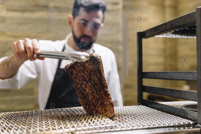 Chef cooking in restaurant preparing beef roast