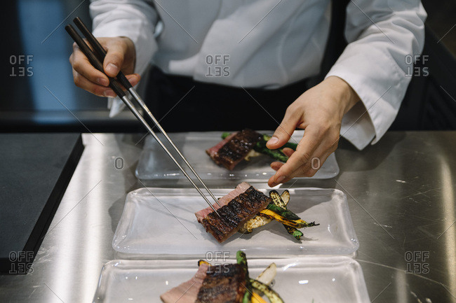 Chef cooking in restaurant prepares the dishes with chopsticks
