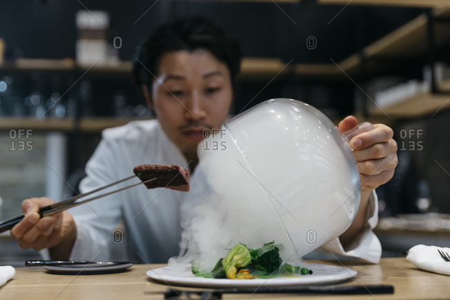 Chef cooking in restaurant with smoke dish