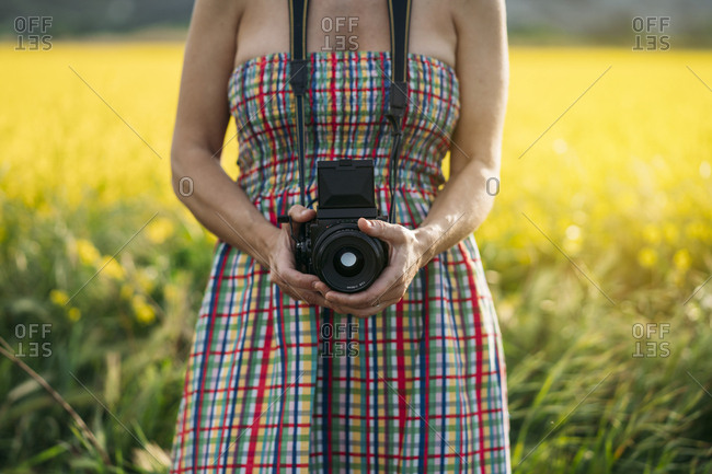 Crop unrecognizable lady in colored dress and jeans jacket holding photo device in nature