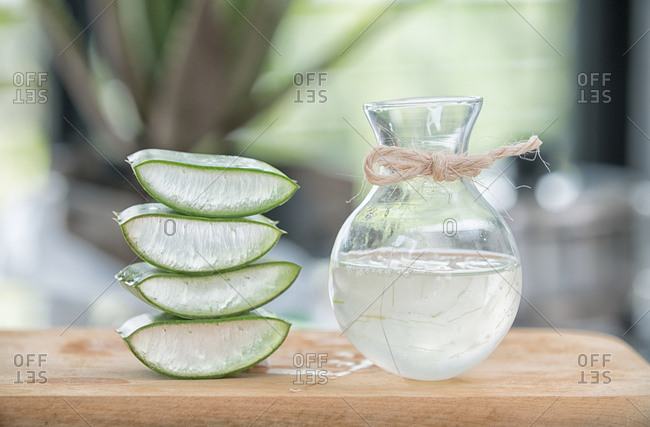 Pieces of Aloe Vera and refreshing drink served in glass jug on the table.