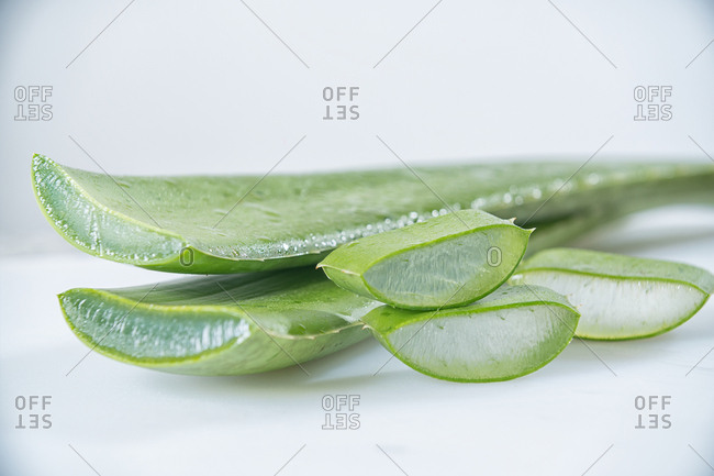 Pieces of fresh green Aloe Vera with white flesh on light background.