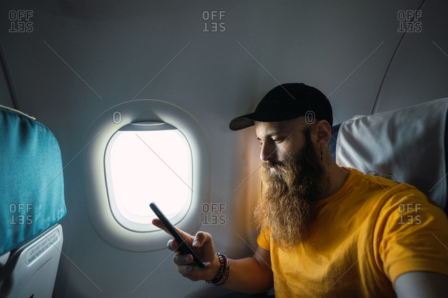 Bearded man with smartphone inside of plane