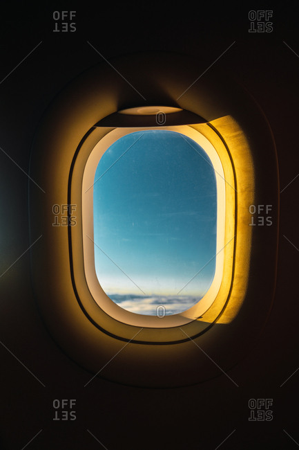 Shot from inside of airplane window with blue sky behind illuminated with golden lights of sunset