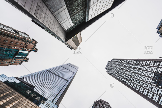From below shot of high-rise contemporary skyscrapers with glass reflecting daylight under clear sky