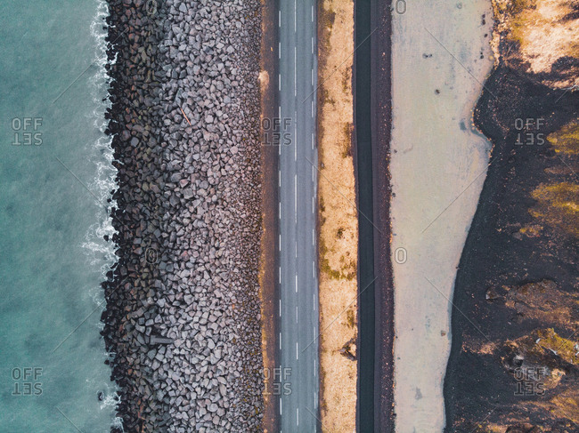 From above shot of narrow asphalt road going along stone shore of sea in North Iceland
