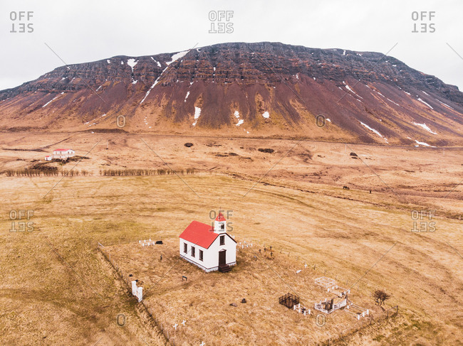 Small church standing in dry valley near high hill in North Iceland
