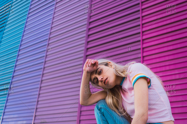 Woman sitting at multicolored wall