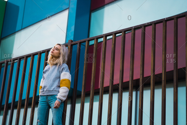 Pretty blonde woman standing at fence on background on colorful modern houses.