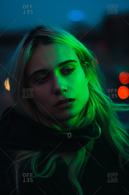 Thoughtful blonde woman with green light on face standing on street in the dusk.