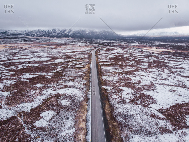 View from above of asphalt road in Iceland through snowy open space with clouds and mountains