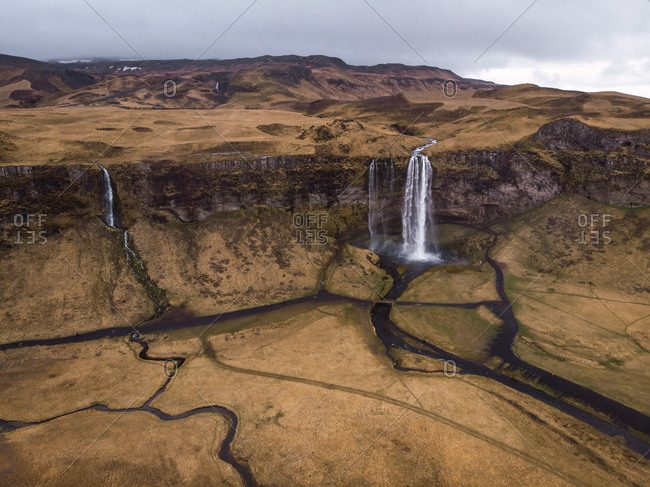 View from above of epic waterfall and valley with rivers in Iceland