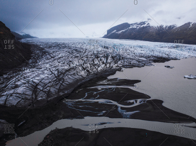 View from above of Icelandic glacier and mere with black sand