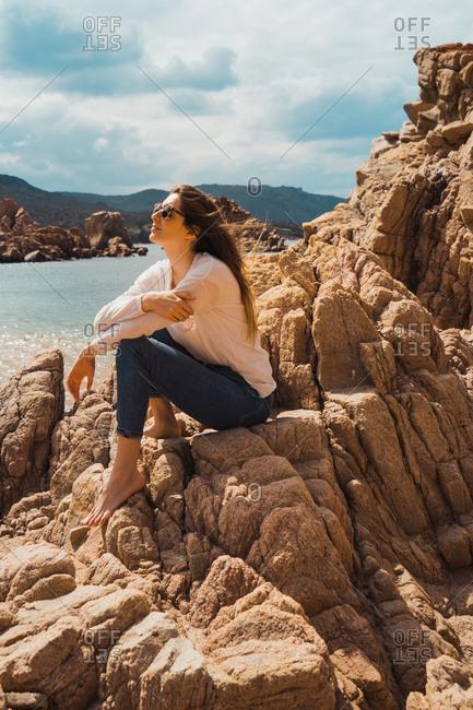 Woman sitting on rocks at seaside