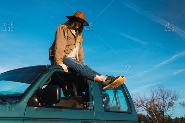 Woman sitting on car roof