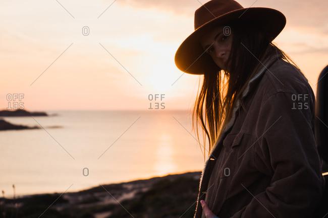 Dreamy woman in hat at seaside