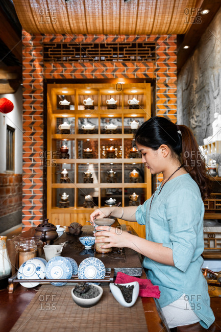 Young Asian woman making preparations and brewing oriental tea