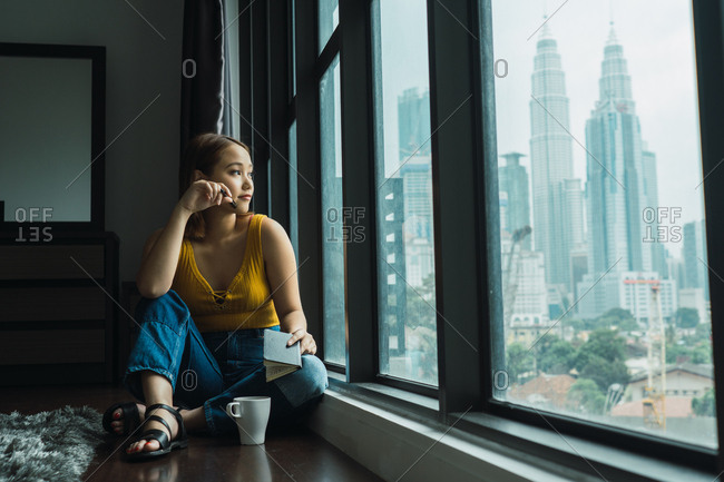 Woman with cup at window