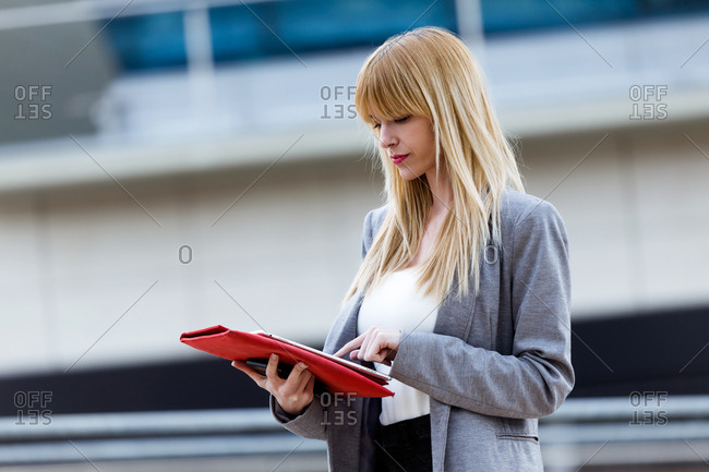 Beautiful blonde female in suit standing on street and using tablet