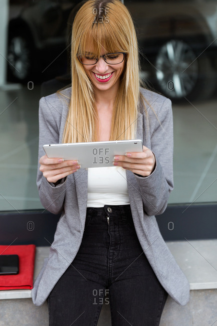 Smiling young lady in glasses and business style using her white device with car on background