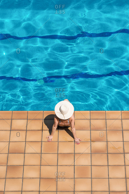 Woman swimming in a pool on a sunny day on summer vacation