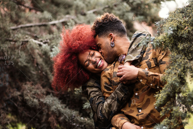 Trendy African-American couple standing among green trees and kissing in embrace with happiness