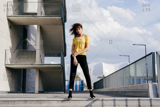 Pretty young woman in sportswear standing on the street and looking at camera.
