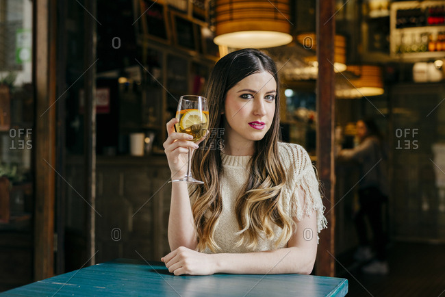 Cheerful dreamy woman with drink