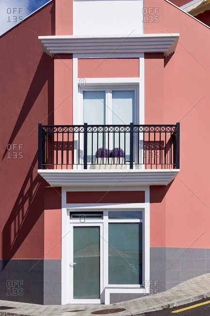 Balcony with purple flowers on small red house on street in The Palm, Spain.