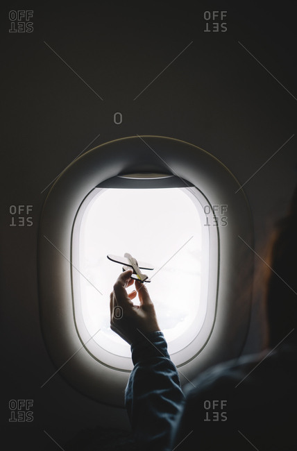 Woman shows airplane model in window.
