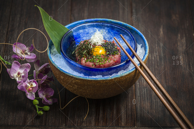 Chopsticks and flowers lying near bowl with ice and savory steak tartare with raw egg on timber tabletop
