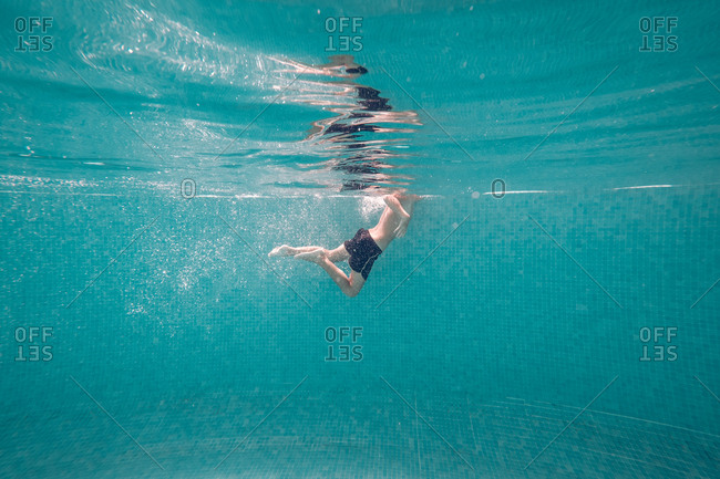 Boy in swimming trunks swims in transparent turquoise deep pool raising air bubbles