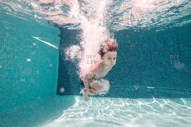 boy in swimming trunks dives into transparent blue pool water.