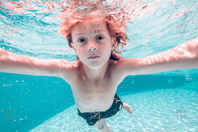 Red-haired child completely dives in water and smiling looking into camera releasing air bubbles from the nose against a background of transparent water