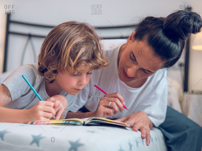 Beautiful woman and cute child lying on comfortable bed and coloring pictures in notebook together.