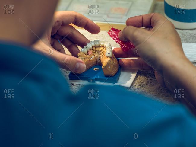 Crop hands holding denture