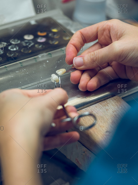 Crop hands of dental technician holding carefully two pieces of enamel while making veneers in lab