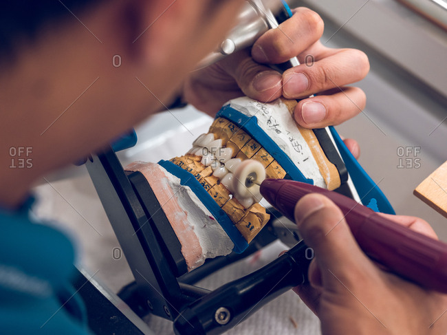 Crop man using polisher to polish artificial teeth on denture while working in dental laboratory.