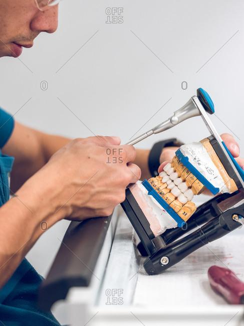 Dental technician holding artificial teeth on holder