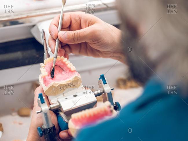 Crop man applying substance on denture