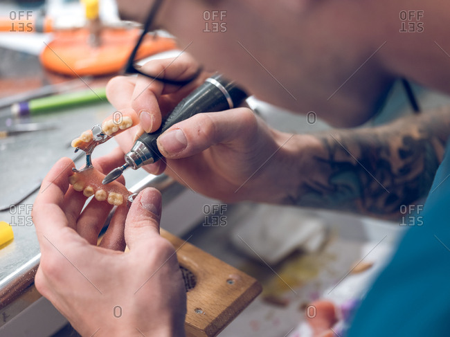 Dental technician polishing teeth