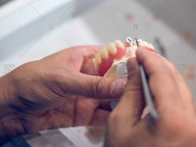 Crop hands carving teeth