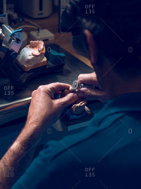 Dental technician polishing teeth