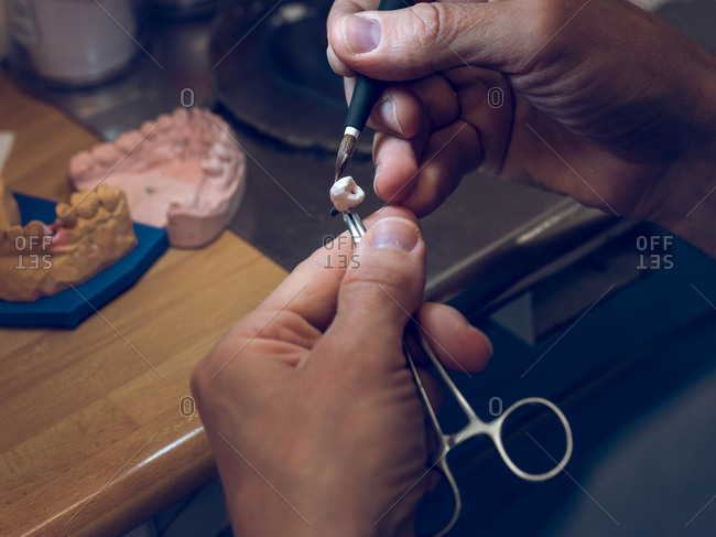 Crop hands of dental technician using tools to carve artificial tooth manually