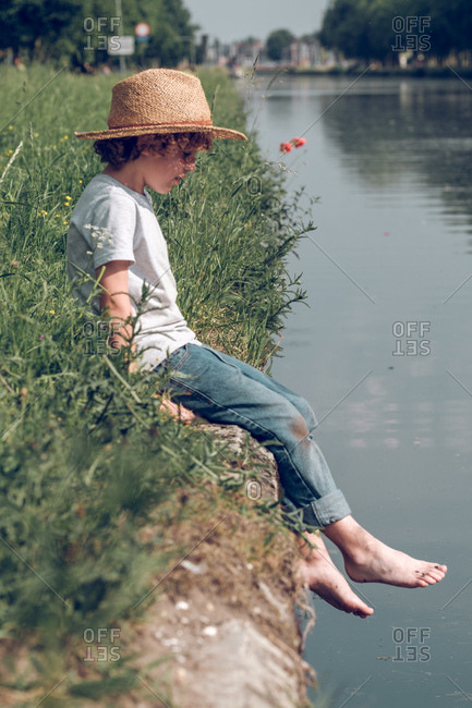 Side view of little boy in casual outfit and straw hat sitting on edge or river waterfront in bright sunlight