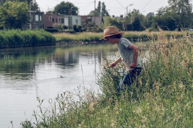 Little boy standing near water