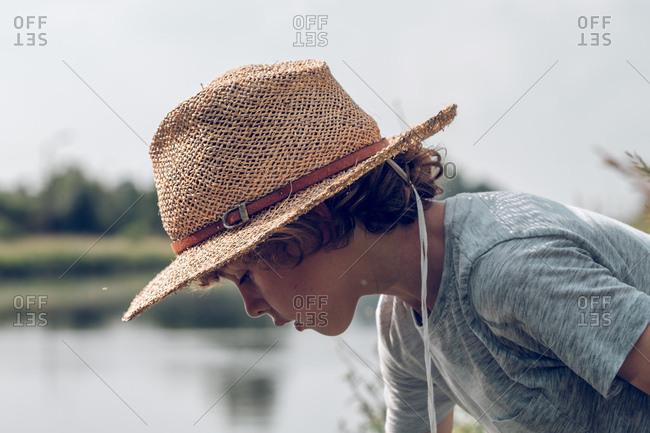 Little boy sitting near water